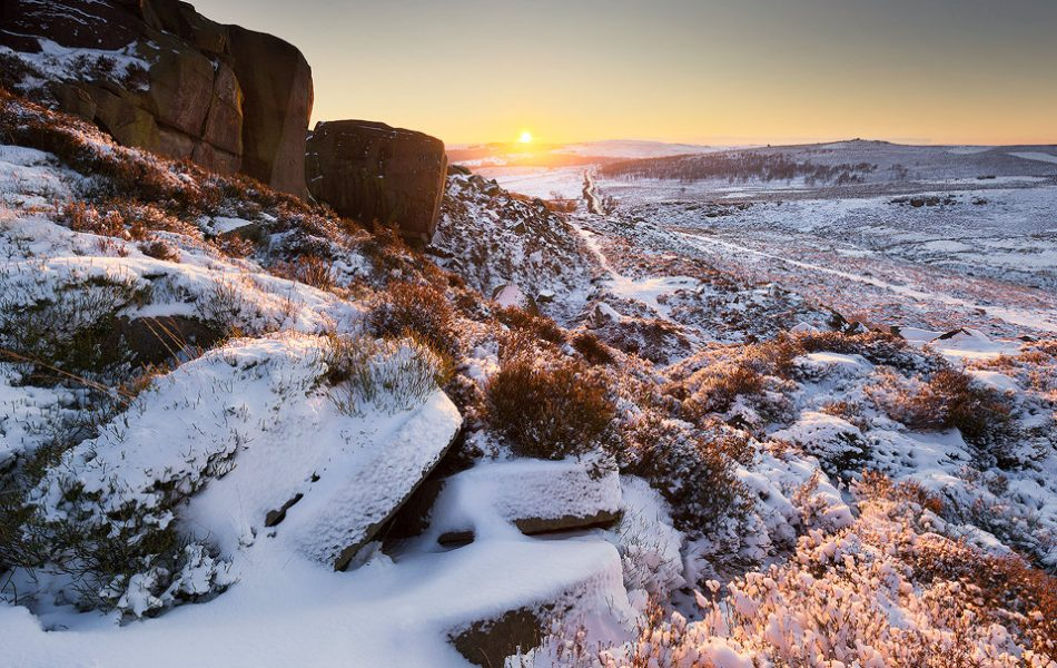 Burbage Edge Millstones in Snow. After sunrise one morning on Over Owler Tor I decided to spend the whole day out in the snow, finishing with sunset at Burbage Edge. I've photographed these abandoned millstones many times over the years but never before with a coating of snow. When I arrived I was pleasantly surprised to find that no one else had passed by yet and the snow was still nice and fresh! In contrast to the overcast morning there wasn't a cloud in the sky and the sun created a beautiful warm glow as it dipped below the horizon.