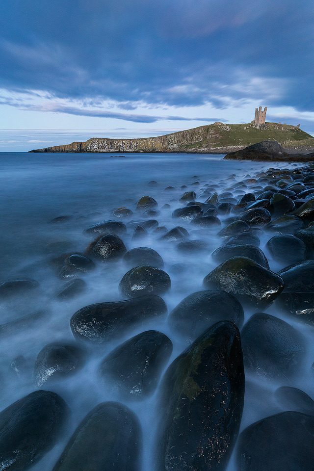 Classic view of the black Embleton boulders looking towards the imposing shape of Dunstanburgh Castle.