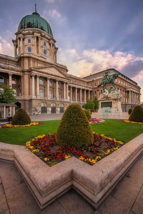 Buda Castle at sunset with some lovely flowers and rays of light coming from the sun. Buda Castle, Budapest Hungary.