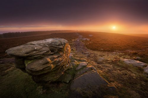 Ox stones Sunrise. With thick fog forecast for most of the Peak District, I decided to take a chance and catch the dawn at the Ox Stones. Just as the forecast had predicted though I arrived in thick murky fog. Not easily put off, I climbed on top of the stones and set up. As I waited the fog got thicker by the minute, it was starting to look like I wouldn't get a sunrise at all. Suddenly a patch of colour appeared on the horizon and light began to burn through the fog, creating a beautiful orange glow and illuminating the gritstone. A beautiful morning!