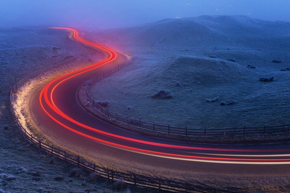 Light trails at the famous winding Mam Nick road below Mam Tor. Temperature: -5 with freezing fog. Derbyshire, Peak District National Park. This is an image I've had in mind for a long time now but have been waiting for the right conditions. It was absolutely freezing sat waiting for the cars to come by, every blade of grass was covered in thick frost and I could barely see anything in the thickest patches of drifting fog. Everything came together in the end though, and after capturing a few light trails I headed back home to the warmth. ABOUT MAM TOR: Mam Tor is a 517m hill near Castleton, in the High Peak area of the Peak District National Park. The hill gets its nickname 'The Shivering Mountain' from the frequent landslips that occur on the eastern face of the hill, caused by unstable layers of shale. At the base of Mam Tor and at nearby Winnats Pass are four famous caverns where semi precious minerals such as Blue John were once mined. These caverns are known as; the Blue John Cavern, the Peak Cavern, the Speedwell Cavern, and the Treak Cliff Cavern.
