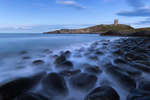 Classic view of the black Embleton boulders looking towards the imposing shape of Dunstanburgh Castle. After photographing the sunrise at Craster we decided to visit the famous viewpoint at Embleton for the blue hour.