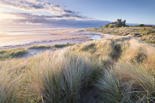 Beautiful summer sunrise at the iconic Bamburgh Castle on the North East Coast. After photographing the sunset and blue hour around Dunstanburgh we headed to Bamburgh for the sunrise. After an unpromising start the sun eventually managed to break through the low band of cloud and we got some stunning light.