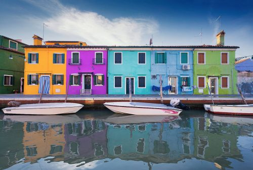 Colourful Burano houses reflected in one of the many picturesque canals running through the historic streets. We visited Burano on a beautifully sunny clear blue sky day, these conditions are not always best for photography, but the bright blue sky added another variation of colour to the multicoloured Burano houses.