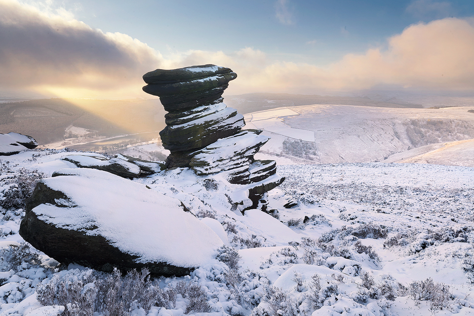 Salt Cellar in Winter. Some fantastic wintry conditions at the Salt Cellar on Derwent Edge in the Peak District National Park. I've visited this location many times over the years, never quite getting the right conditions. On this occasion hoar frost, snow, low cloud and some sublime light combined for a spectacular Winter wonderland. On this afternoon I was blessed with some stunning conditions, particularly when this well defined beam of light broke through the clouds illuminating the snowy hills in the distance.
