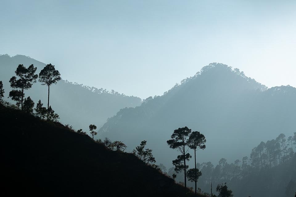 Late afternoon sunshine streams through the moody sky illuminating the layered hills of Sattal. Nainital, Uttrarakhand, India