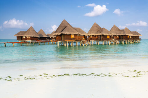 Luxury villas on stilts over the crystal clear waters and white sandy beaches of the maldives under a bright blue sky.